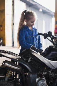 little-girl-overall-inspecting-quad-bike
